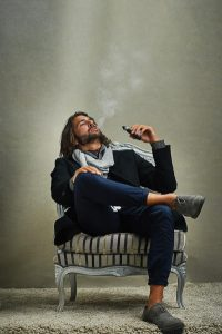man relaxing and vaping whilst sitting