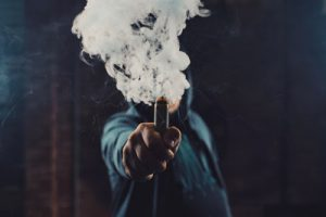 Vaper holding e cigarette with vapour cloud