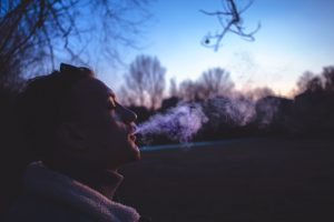 Man Puffing E-Cigarette Clouds